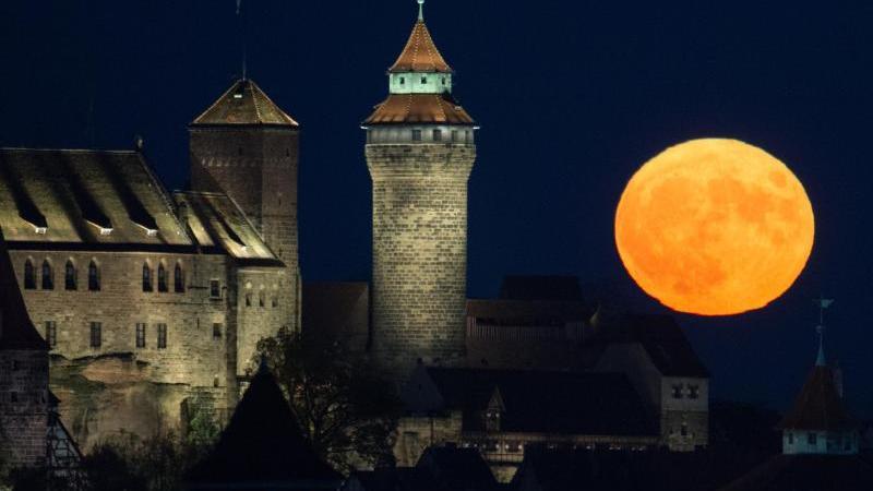 Der Vollmond geht hinter der Kaiserburg auf. Foto: Timm Schamberger/dpa/Archivbild