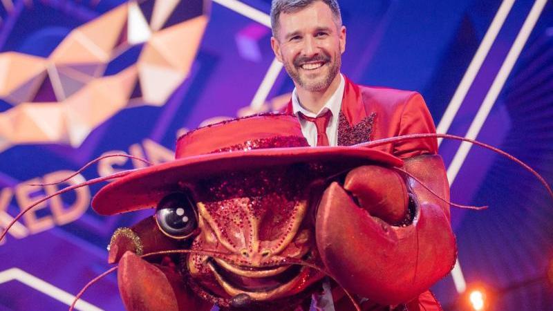 """Jochen Schropp steht als enttarnte Figur """"Der Hummer"""" in der Prosieben-Show """"The Masked Singer"""" auf der Bühne. Foto: Rolf Vennenbernd/dpa"""