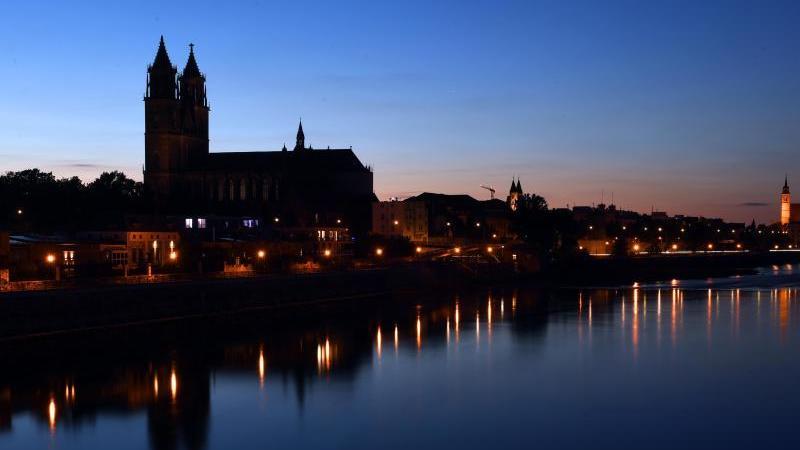 Die Silhouette des Doms nahe der Elbe zeichnet sich in der Abenddämmerung vor dem dunklen Himmel ab. Foto: Hendrik Schmidt/dpa-Zentralbild/dpa/Archivbild