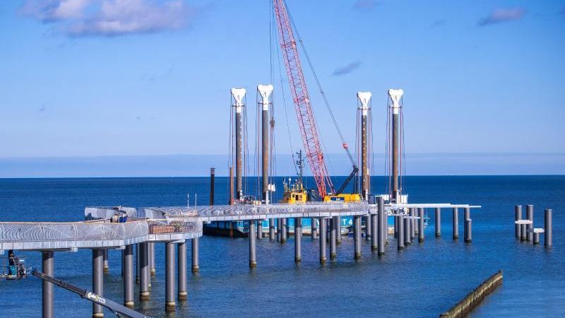 Mit einem Mobilkran auf einem Ponton wird die neue Seebrücke am Strand der Insel Usedom aufgebaut. Foto: Jens Büttner/dpa-Zentralbild/dpa/Archivbild
