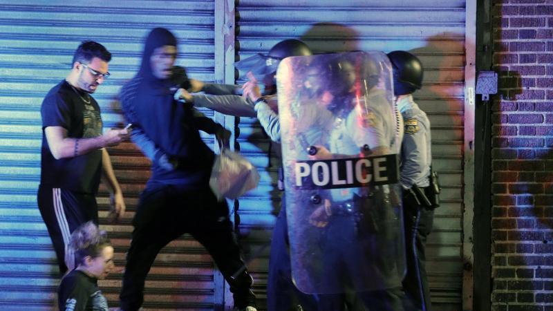 Demonstranten geraten mit Polizisten aneinander. Foto: Elizabeth Robertson/The Philadelphia Inquirer/AP/dpa
