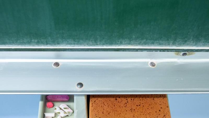 Schwamm und Kreide liegen in einem Klassenraum unter einer Tafel. Foto: Klaus-Dietmar Gabbert/dpa-Zentralbild/ZB/Symbolbild