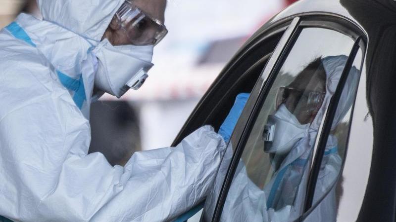 Ein Mitarbeiter eines Korona-Testzentrums auf dem Marburger Messegelände nimmt einen Abstrich von einem Autofahrer. Foto: Boris Roessler/dpa