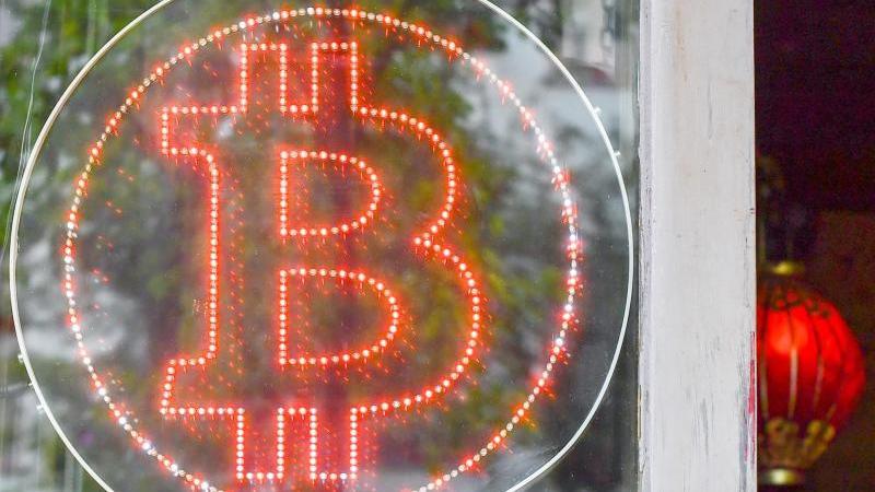 Ein Bitcoin-Logo in einem Schaufenster einer Kneipe im Kreuzberger Graefekiez. Foto: Jens Kalaene/ZB/dpa