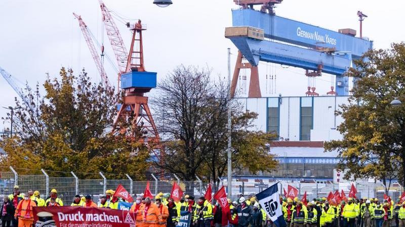 Teilnehmer einer Demonstration gehen auf einer Straße vor der Kieler Werft German Naval Yards. Foto: Frank Molter/dpa