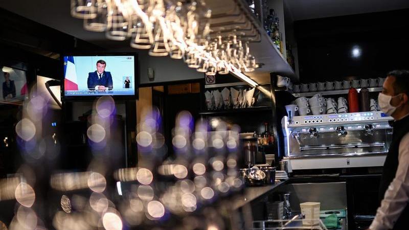 Ein Barkeeper schaut sich die Fernsehansprache von Präsident Macron in einem Café in Marseille an. Foto: Christophe Simon/AFP/dpa