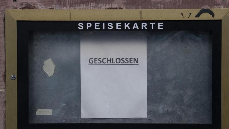 """Ein Zettel mit der Aufschrift """"Geschlossen"""" hängt vor einem Restaurant. Foto: Boris Roessler/dpa/Symbolbild"""