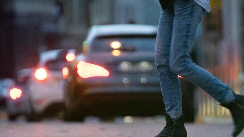 Eine Fußgängerin geht im Morgenverkehr über einen Straße. Foto: Sebastian Gollnow/dpa/Symbolbild