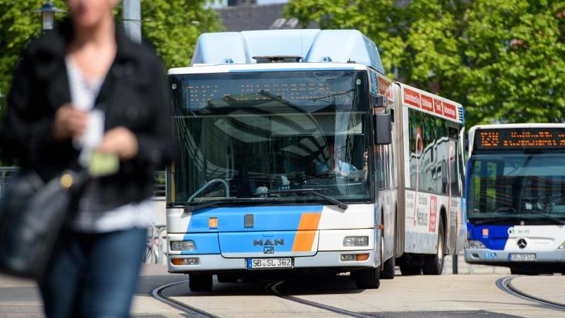 Zwei Busse des Saarländischen Verkehrverbundes (ÖPNV) fahren eine Haltestelle an. Foto: Oliver Dietze/dpa/Archivbild
