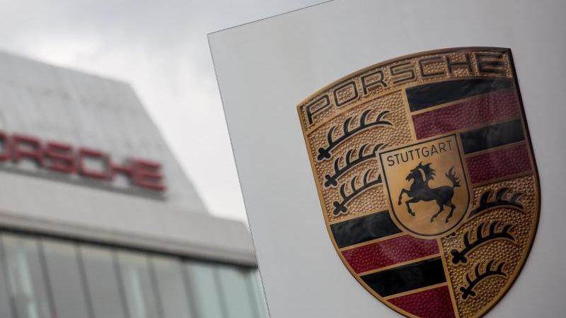 Das Porsche Logo ist vor einem Gebäude des Automobilherstellers zu sehen. Foto: Christoph Schmidt/dpa/Archivbild