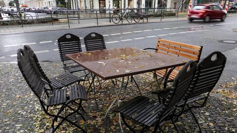Nasses Laub bedeckt Stühle und Tische auf einem geschlossenen Freisitz. Foto: Jan Woitas/dpa-Zentralbild/dpa/Archivbild