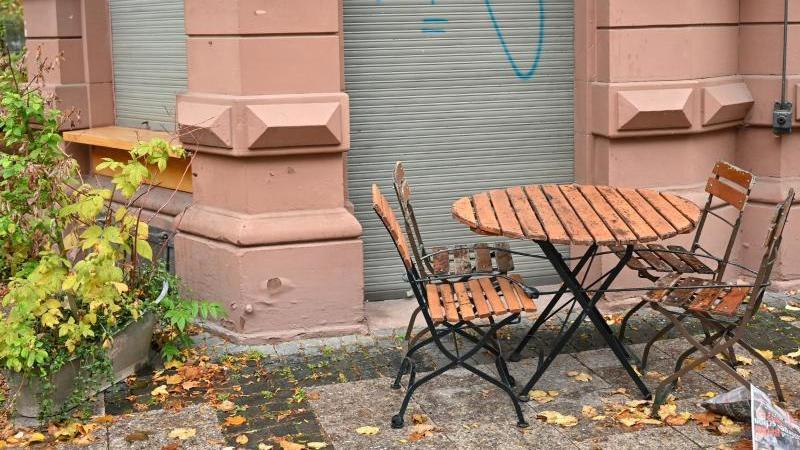 Tisch und Stühle stehen auf der Frankfurter Zeil vor einem geschlossenen Café. Foto: Arne Dedert/dpa/Archivbild
