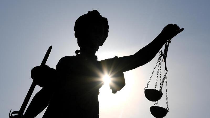Die Statue der Justitia steht im Gegenlicht der Sonne. Foto: Arne Dedert/dpa/Symbolbild
