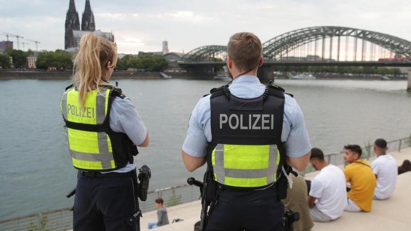 Zwei Polizisten kontrollieren die Einhaltung des coronabedingten Sicherheitsabstandes. Foto: David Young/dpa/Archivbild