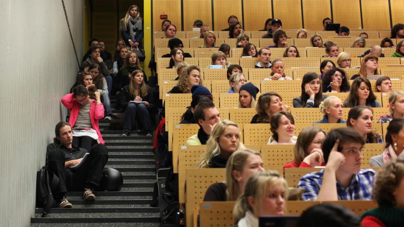 ARCHIV- Studenten sitzen am 17.10.2011 in einem Hörsaal der Ruhr-Universität in Bochum teilweise auf den Treppen und hören eine Vorlesung der Amerikanistik. Bund und Länder fürchten auch zum kommenden Herbst erneut ein Einschreibchaos an den Hochsch