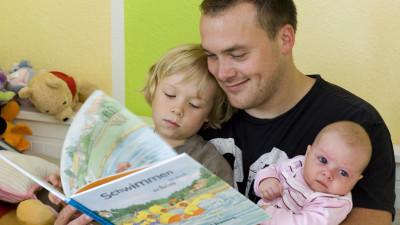 Vater liest seinen Kindern etwas vor
