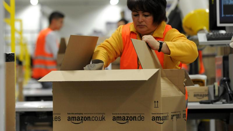 Ein Mitarbeiterin der Versandabteilung des Amazon Logistikzentrums in Pforzheim (Baden-Württemberg) legt am 11.12.2012 Waren in ein Paket. Das Weihnachtsgeschäft von Amazon läuft auf Hochtouren, auch das neue Logistikzentrum in Pforzheim mischt kräft