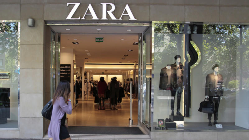 ARCHIV - Eine Frau geht in Madrid an einer Filiale der Modekette Zara in Madrid vorbei (Archivfoto vom 21.09.2011). Der weltgrößte Mode-Einzelhändler und Betreiber der Modekette Zara hat mit wachsendender Konkurrenz und schwachen Märkten in den Euro-