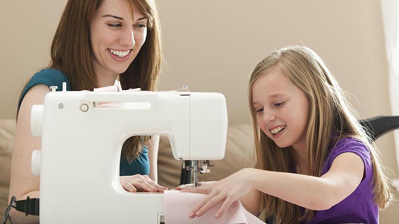 Junge Frau arbeitet an der Nähmaschine, Kind hilft