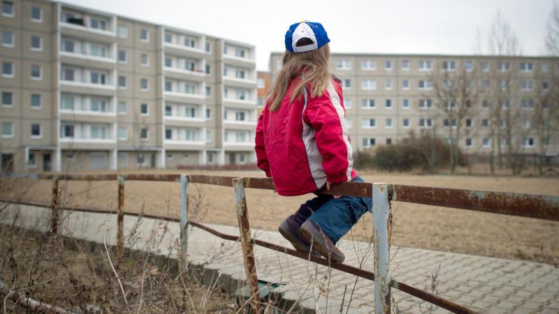 ARCHIV- ILLUSTRATION - Ein kleines Mädchen sitzt am 13.03.2012 allein auf einem rostigen Geländer im Innenhof eines Plattenbau-Wohngebiets in Frankfurt (Oder). Das Deutsche Kinderhilfswerk stellt am 14.01.2014 eine Umfrage zur Kinderarmut in Deutsch