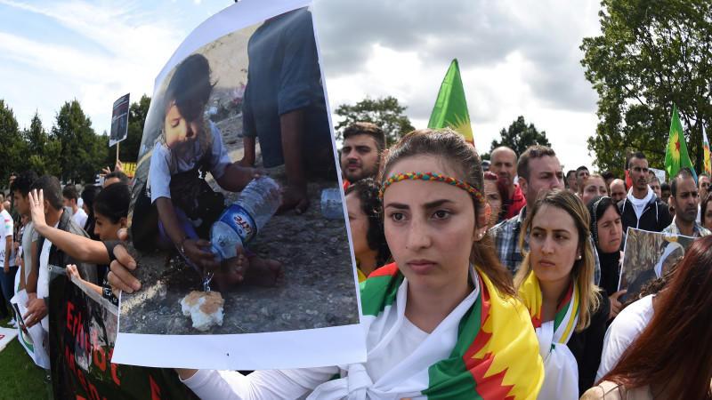 Eine Demonstrantin steht mit dem Bild eines Kindes bei der Abschlusskundgebung in Hannover.