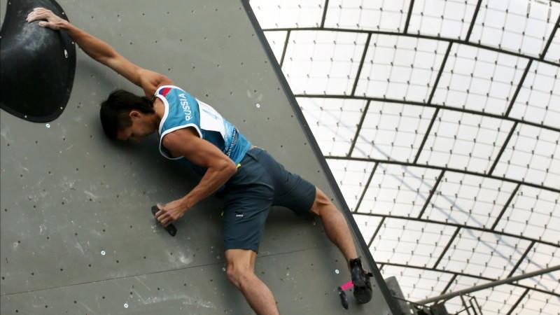 Teilnehmer der Boulder-Weltmeisterschaft in München erklimmt eine Kletterwand.