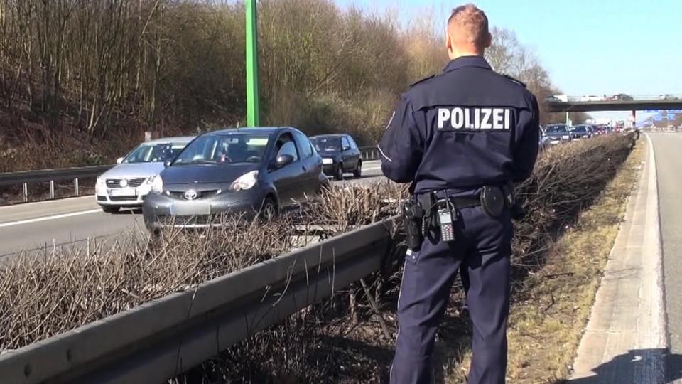 Ein Polizist schreibt die Nummernschilder der Gaffer auf.