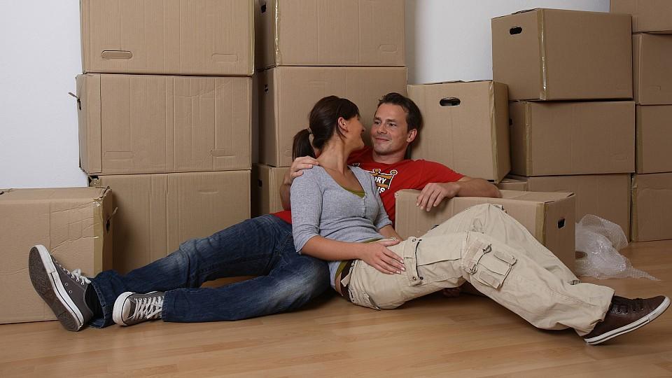 junges Paar beim Umzug sitzt am Boden, macht Pause und schaut sich verliebt an  | young couple moving house and taking a break