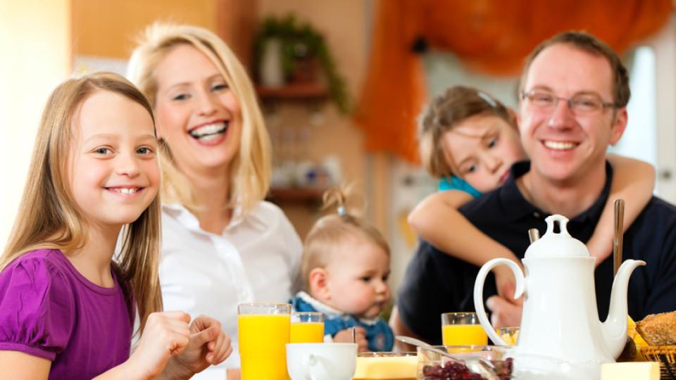 Familie mit Kinder isst gemeinsam am Tisch