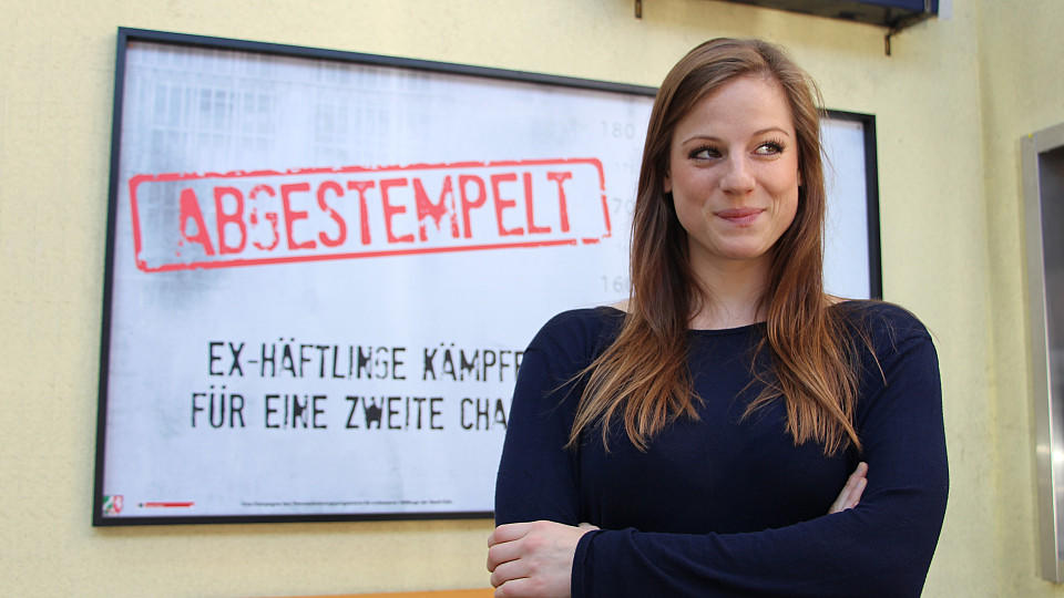 """Unter uns""""-Star Nora Koppen vor einem Plakat in der Schillerallee"""