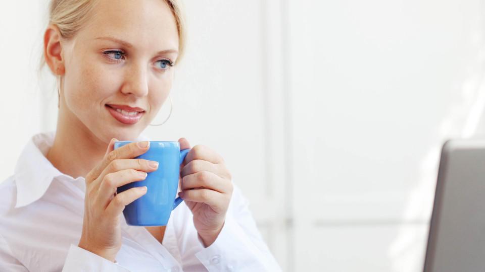 Eine Frau sitzt Kaffee trinkend vor ihrem Laptop