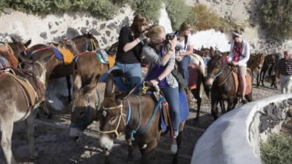 Urlauber in Griechenland reiten auf Eseln.