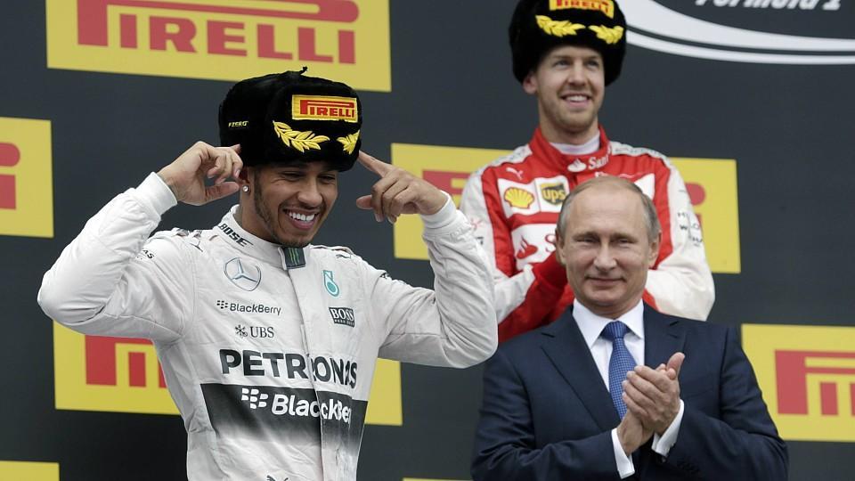 SOCHI, RUSSIA. OCTOBER 11, 2015. Russia s president Vladimir Putin (R front), race winner British racing driver Lewis Carl Davidson Hamilton (L) representing Mercedes AMG, and first runner-up, German racing driver Sebastian Vettel (R back) representi