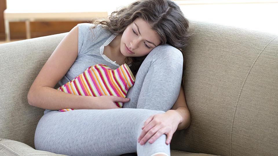 Frau liegt mit Wärmflasche auf dem Sofa