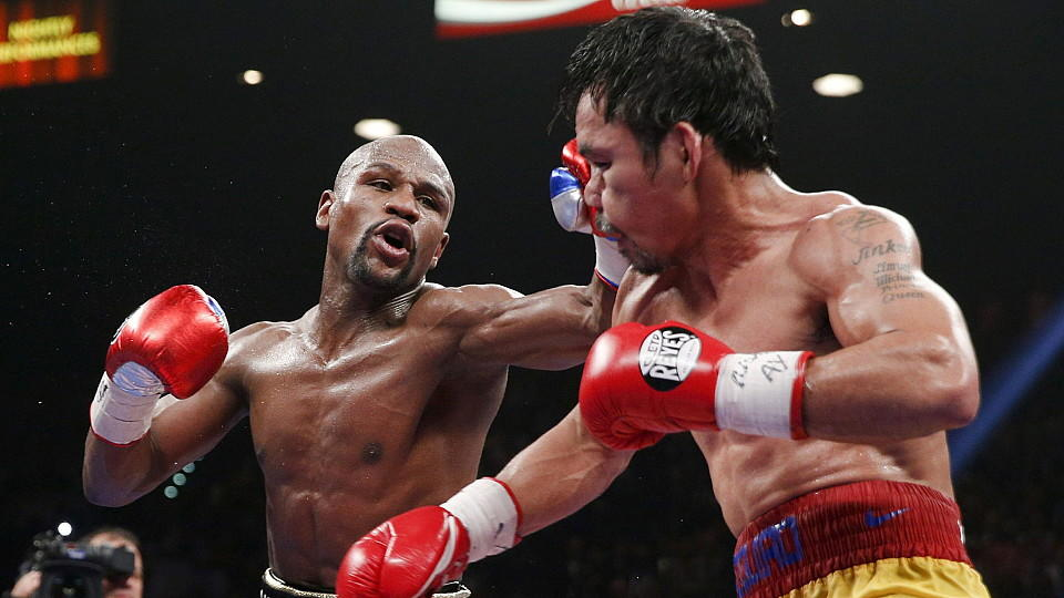 epa04730884 Floyd Mayweather Jr. (L) throws a left against Manny Pacquiao during their welterweight unification championship boxing fight at the MGM Grand Garden Arena in Las Vegas, Nevada, USA, on 02 May 2015. EPA/ESTHER LIN +++(c) dpa - Bildfunk+++
