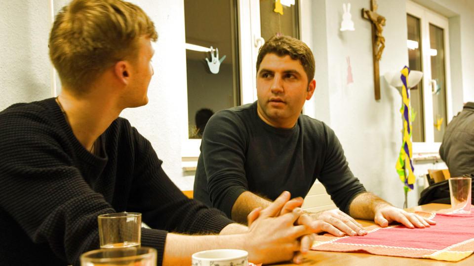 Hassan (re.) unterhält sich mit dem Flüchtlingshelfer Pascal auf Deutsch.