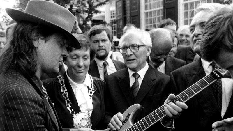 """Udo Lindenberg überrreicht Erich Honecker bei dessen Besuch 1987 in Wuppertal eine - laut Lindenberg - """"nicht ganz billige Gitarre"""" mit der Aufschrift """"Gitarren statt Knarren"""" übereicht. Foto: Franz-Peter Tschauner"""