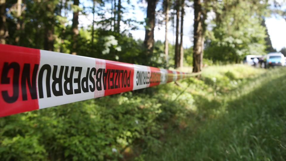 Ein Absperrband der Polizei umzäunt am 04.07.2016 ein Waldstück an einer Verbindungsstraße zwischen Rodacherbrunn in Thüringen und Nordhalben in Bayern. Nach dem Fund einer Leiche in einem Waldstück in Thüringen prüfen die Ermittler Verbindungen zum