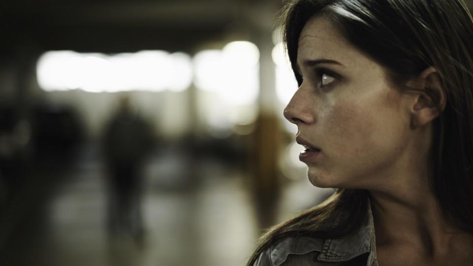 Psychose, Verfolgungswahn: Eine Frau blickt ängstlich nach hinten