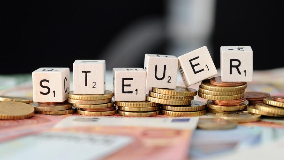 ARCHIV - ILLUSTRATION - Würfel mit Buchstaben «Steuer» liegen am 04.11.2014 in München (Bayern) auf Geldmünzen und Geldscheinen. In Nordrhein-Westfalen wird derzeit eine erste Gruppe griechischer Steuerbeamter geschult. Foto: Tobias Hase /dpa (zu dpa