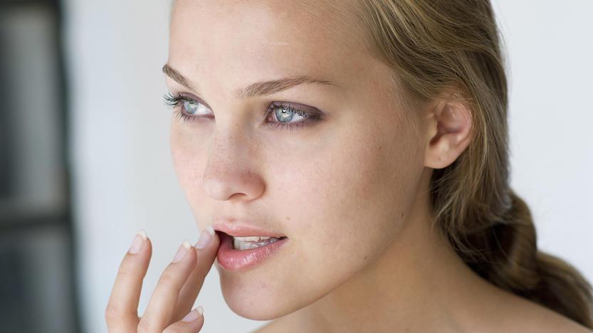 Junge Frau trägt Lippenbalsam auf Keine Weitergabe an Drittverwerter.