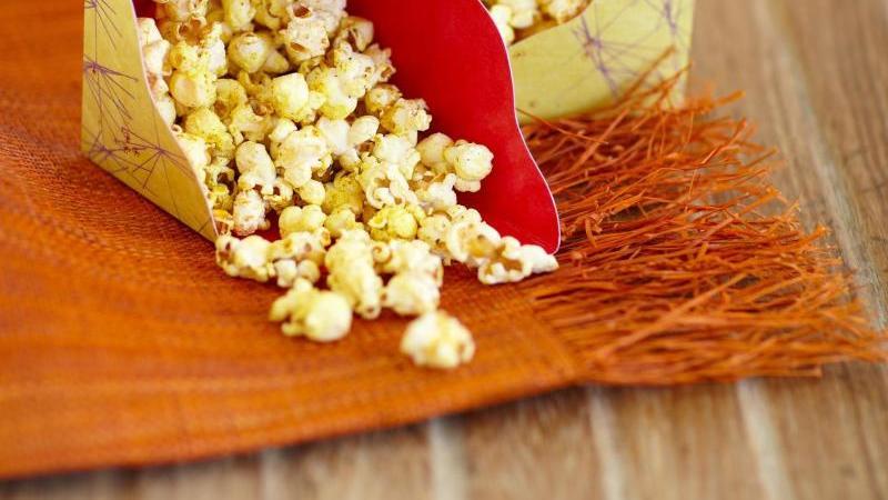 """Würzig wird es bei diesem Rezept aus dem Kochbuch """"Popcorn!"""":Garam Masala trifft auf Kurkuma und Chilipulver. Alles zusammen wird über das heiße Popcorn gegeben. Foto: Adrian Lawrence"""