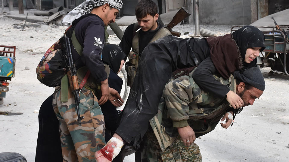 A Syrian pro-government fighter carries a wounded woman who was reportedly shot by rebel sniper while fleeing with her family Aleppo's eastern al-Salihin neighbourhood on December 12, 2016 after troops retook the area from rebel fighters. / AFP / GEO