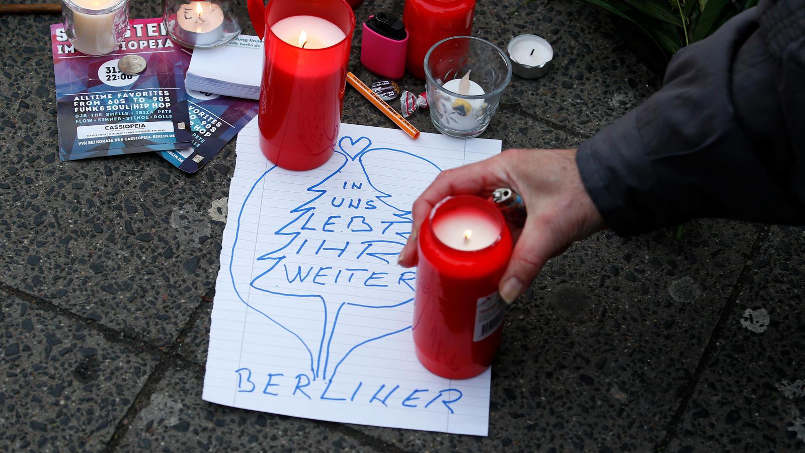 Auf dem Weihnachtsmarkt in Berlin legen Menschen Kerzen, Bilder und Blumen ab, um der Opfer zu gedenken.