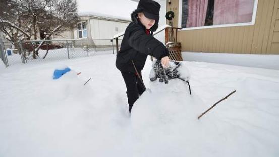 Der kleine Billy Larsen (6) kann es kaum glauben - Schneemänner in seinem Garten.