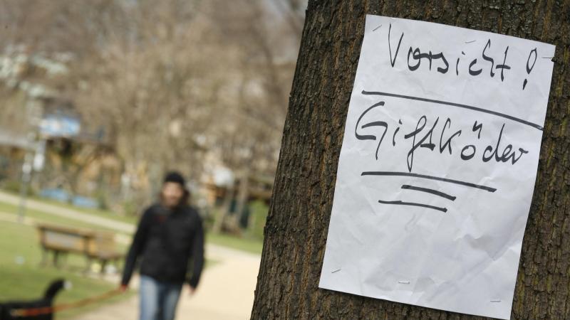 Ein Zettel warnt in einem Park vor Giftködern. Foto: Florian Schuh/Archiv