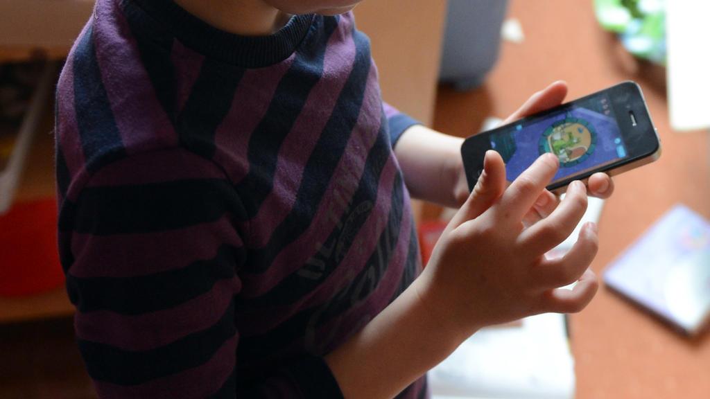 ARCHIV- ILLUSTRATION - Ein Junge spielt in seinem Kinderzimmer auf einem Smartphone ein Computerspiel, aufgenommen am 10.04.2012 in Berlin. Sieben von zehn Kindern im Krippen- und Kita-Alter nutzen Ärzten zufolge das Handy ihrer Eltern mehr als eine