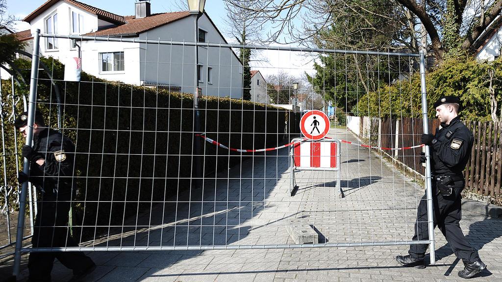 Polizisten bringen an einem Weg im Stadtteil Freimann in München ein Absperrgitter an.
