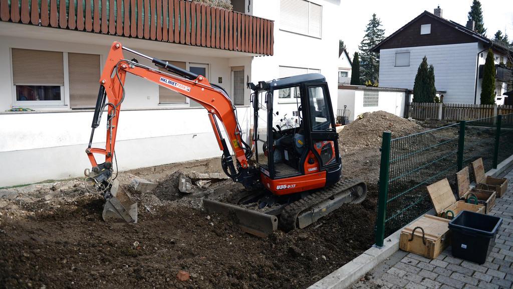 Ein Bagger steht vor einem Haus im Stadtteil Freimann in München, in dessen Garten große Mengen an Sprengstoff gefunden wurden.