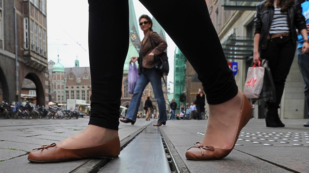 Eine Frau betritt am Dienstag (05.07.2011) die glatte Stahlschiene auf der Obernstraße in der Innenstadt von Bremen. Seit Jahren rutschen Fußgänger immer wieder auf dem blanken Metallstreifen zwischen Straßenbahnschienen und Fußweg aus. Kleine Stahln